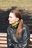 Femme s'asseyant sur un banc Photo stock