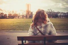 Femme s'asseyant sur un banc de parc Photos stock