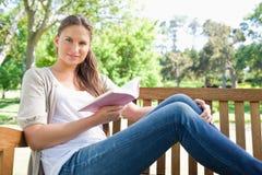 Femme s'asseyant sur un banc de parc avec un livre Photographie stock libre de droits