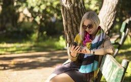 femme s'asseyant sur un banc de parc et dactylographiant sur son smartphone Photos stock