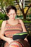 Femme s'asseyant sur un banc de parc et lisant l'eBook Photographie stock