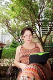 Femme s'asseyant sur un banc de parc et lisant l'eBook Images libres de droits