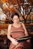 Femme s'asseyant sur un banc de parc et lisant l'eBook Photo stock