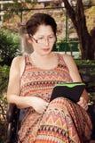 Femme s'asseyant sur un banc de parc et lisant l'eBook Photo libre de droits