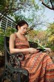 Femme s'asseyant sur un banc de parc et lisant l'eBook Image stock