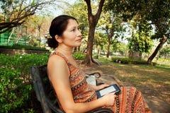 Femme s'asseyant sur un banc de parc et lisant l'eBook Photos libres de droits