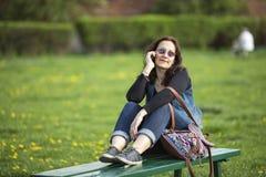 Femme s'asseyant sur un banc de parc parlant à un téléphone portable Amour Photographie stock