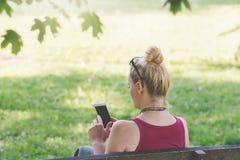Femme s'asseyant sur un banc de parc, textotant à son téléphone Images libres de droits