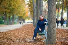 Femme s'asseyant sur un banc en parc Image stock