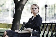 Femme s'asseyant sur un banc en stationnement images stock