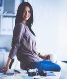 Femme s'asseyant sur un sofa dans sa maison avec l'appareil-photo photographie stock