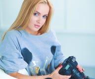 Femme s'asseyant sur un sofa dans sa maison avec l'appareil-photo image stock