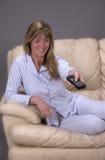 Femme s'asseyant sur un sofa tenant un contrôleur à distance pour une TV images libres de droits