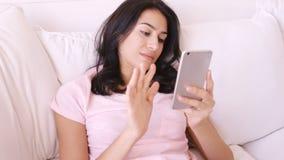 Femme s'asseyant sur un sofa utilisant son smartphone banque de vidéos