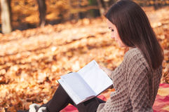 Femme s'asseyant sur une couverture et un livre de lecture Photo stock
