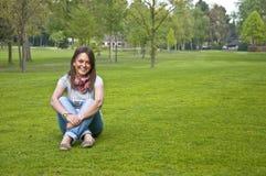 Femme s'asseyant sur une herbe verte Photos libres de droits