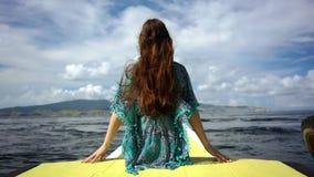 Femme s'asseyant sur une jetée dans un jour de détente d'été pendant des vacances banque de vidéos