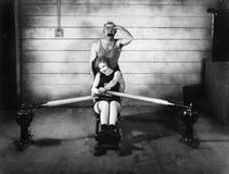 Femme s'asseyant sur une machine à ramer avec un homme derrière elle (toutes les personnes représentées ne sont pas plus long viv photographie stock