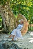 femme s'asseyant sur une oscillation à la plage Photos libres de droits