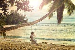 femme s'asseyant sur une oscillation à la plage Images stock