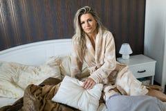 Femme s'asseyant sur une robe de chambre de port de lit image libre de droits