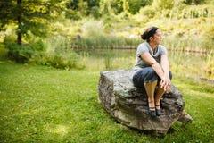Femme s'asseyant sur une roche photos stock