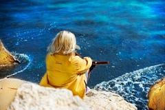 Femme s'asseyant sur une roche par la mer Photos stock