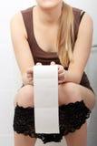 Femme s'asseyant sur une toilette Photo stock