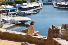 Femme s'asseyante à la côte sur l'île Photos libres de droits