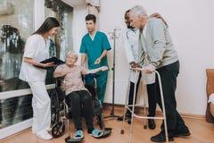 Femme s'asseyante avec le compte-gouttes Patient avec le marcheur photo stock