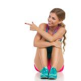 Femme s'asseyante dans des vêtements de sports se dirigeant et regardant loin Photographie stock