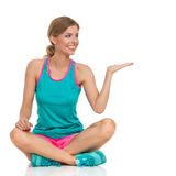 Femme s'asseyante dans la présentation vibrante de vêtements de sports Photo libre de droits