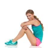 Femme s'asseyante dans la vue de côté de vêtements de sports Photos stock