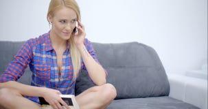 Femme s'asseyante parlant par le téléphone au sofa clips vidéos