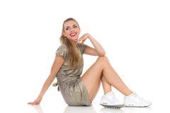 Femme s'asseyante regardant au-dessus de l'épaule Images stock