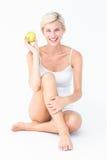Femme s'asseyante tenant une pomme photo stock