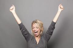 Femme 20s blonde de cri soulevant des mains pour la victoire Images stock