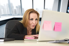 Femme 40s décontractée avec la séance sûre de sourire de cheveux blonds sur la chaise de bureau fonctionnant à l'ordinateur porta Images stock