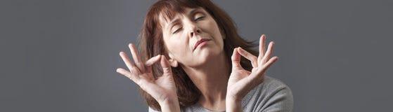 Femme 50s de sourire méditant et détendant avec du yoga, bannière grise Photo libre de droits