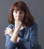 femme 50s entre le sourire et la tristesse Image stock