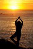 Femme s'exerçant au coucher du soleil sur la côte ouest Photos stock