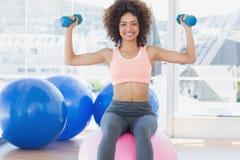 Femme s'exerçant avec des haltères sur la boule de forme physique dans le gymnase Photos stock