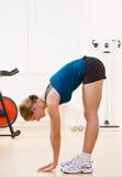 Femme s'exerçant dans le club de santé photo stock