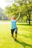 Femme s'exerçant en parc Photos libres de droits