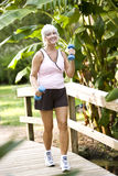 Femme s'exerçant en stationnement marchant avec des poids de main Photographie stock libre de droits