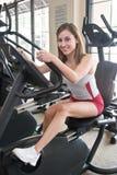 Femme s'exerçant sur le cycle stationnaire Images stock