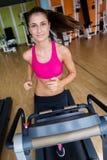 Femme s'exerçant sur le tapis roulant dans le gymnase Photographie stock