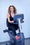 Femme s'exerçant sur le tapis roulant dans le gymnase Image stock