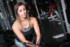 Femme s'exerçant utilisant une machine de câble Photo stock