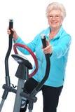 Femme aîné s'exerçant sur de pas Photographie stock